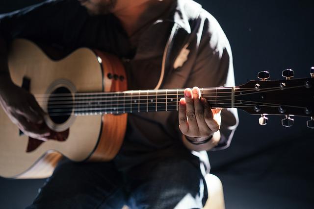 Ein junger Mann spielt auf einer Akustikgitarre.