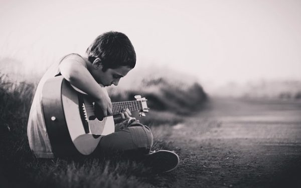 Eine Junge spielt verträumt auf seiner Gitarre.