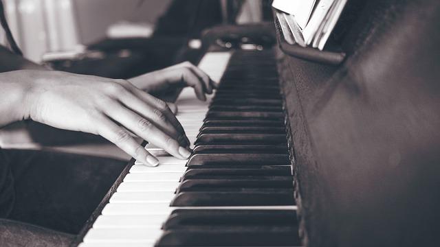 Zwei Frauenhände spielen auf einem Klavier.