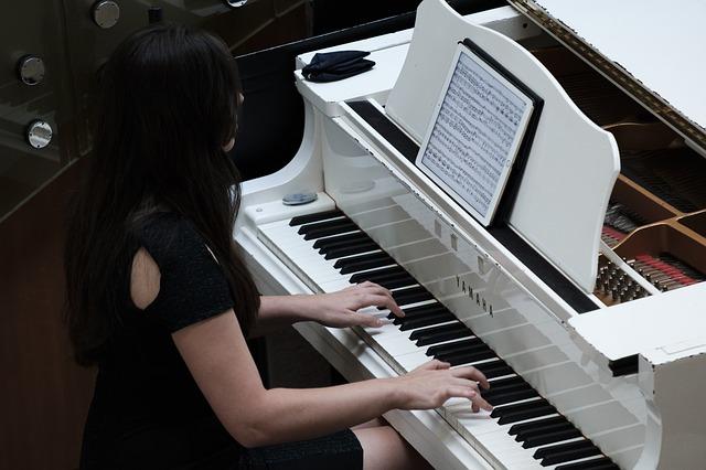 Ein Frau spielt auf einem weißen Klavierflügel. Sie liest Noten von einem Tablet.