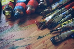 Viele Pinsel und Farbdosen liegen auf einem Holzboden.